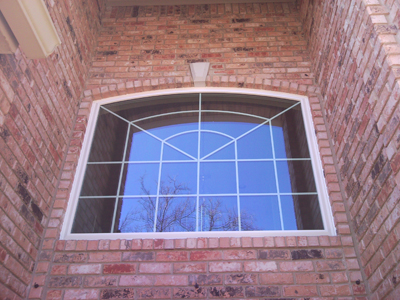 Transome windows with grids in a white vinyl replacement unit.